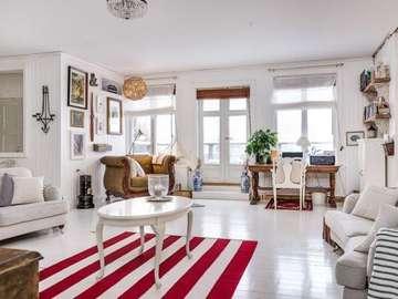Una sala de estar con estilo - Salon z czerwono-białym dywanem.
