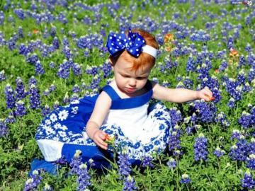 Niña con flores - Una niña en el prado con flores azules.