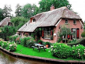 A house in the Netherlands - A beautiful canal house in the Netherlands. The Netherlands is known for its numerous windmills, che