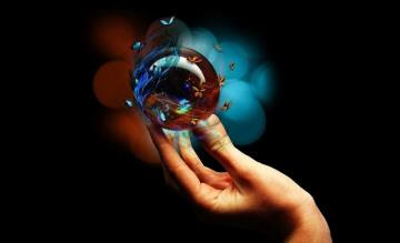 crystal ball - glass ball in hand on a dark background