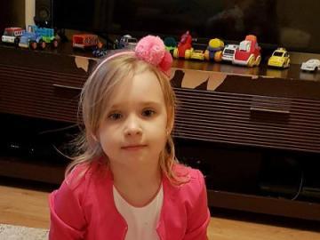 Julia koniec - Una niña sentada entre sus juguetes favoritos.