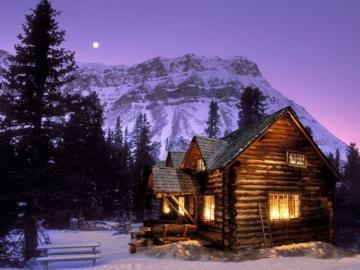 Sera d'inverno - Casa di legno illuminata in piedi ai piedi delle montagne