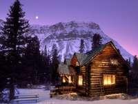 Χειμερινό απόγευμα - Φωτισμένο ξύλινο σπίτι που στέκεται στους πρόποδες τω�