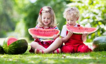 little ones - children are eating watermelons