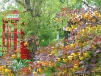 Een bijzondere tuin. - Tuinlandschap met een telefooncel.