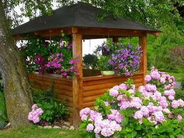 Trädgårdslandskap. - Trädgårdslandskap: lusthus och blommor.