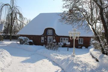 A snow-covered house. - A house with a snow cap on the roof.