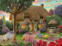 A house, a well and a cat in a - Idyllic Cottage. A house, a well and a cat in a hammock.