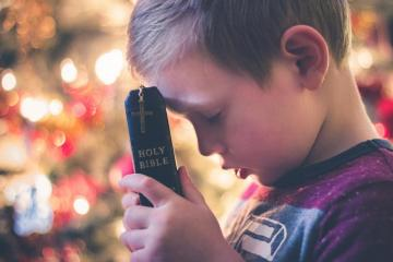 The child is praying in the Bible - The child prays holding the Bible in his hands