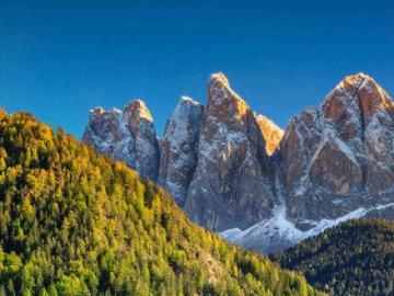 Krajobraz - Dolina i wysokie góry, w dolinie domy.