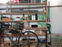 Bicycle in the garage. - Bicycle and a mess in the garage.