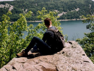 Backpacker over a lake - Person with backpack sitting on gray rock. Chicago
