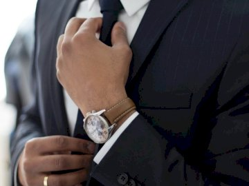 Adjusting the tie - Man wearing watch with black suit.
