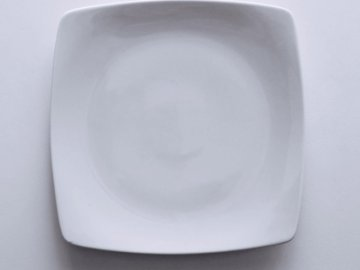 A dish on the table - Empty ceramic plate on white textile. iran