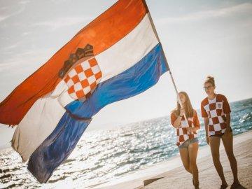 Bandera croata - Persona con bandera del país en la playa.
