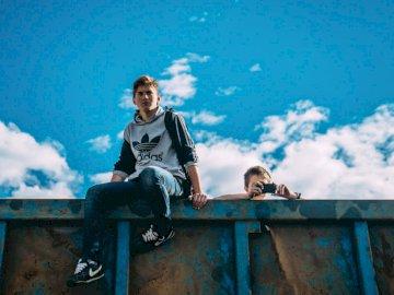 Männer an verrosteter Wand - Mann sitzt auf Schiene neben Mann, der Kamera hält. Russland