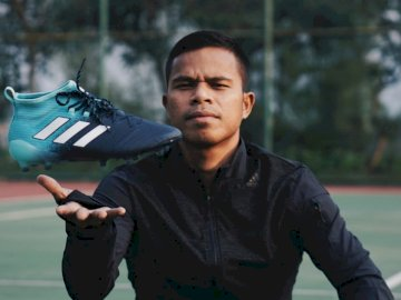 Cleats are an item of footwear - Man in black zip-up jacket holding unpaired blue and black adidas cleat. Bandung