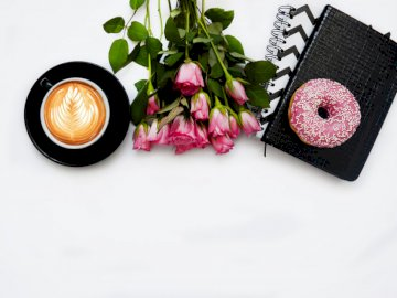 All you need to start your big - Red rose flowers, pink dough nut graphic book and black ceramic cup. Ukraine