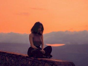 Sam, sport - Kobieta siedzi na klifie. Asila
