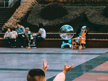 Usually, I'm that individual - Boy reaching bubble near sitting woman during daytime. Beijing, China
