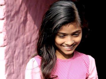 Jeune fille souriante en chemise rose - Jeune fille souriante, debout près du mur.