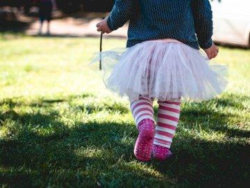 Child in tutu. - Toddler girl wearing teal and white polka-dot long-sleeved shirt and white tutu skirt outfit walking