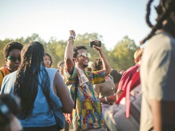 Afropunk Festival was the - Man wearing multicolored shirt dancing in the middle of crowd. NYC