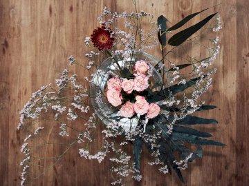 Kwiaty na stole - Różowo-biały wieniec z kwiatów.