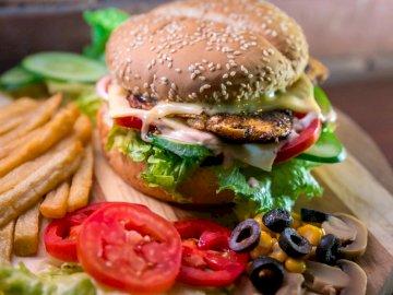 Explosion Burger - Hamburger mit Gemüse und Fleisch neben Pommes. Tallinn, Estland