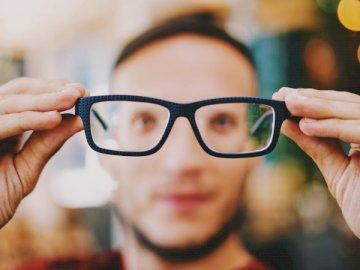 Winzige Augen - Person, die Brillen mit schwarzen Rahmen hält. Griechenland