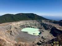 Poas Volcano - Aerial view of lake in the middle of mountains during daytime.