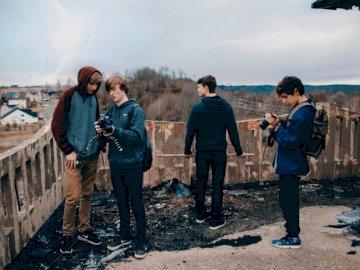Gente en edificio abandonado - Cuatro hombres vestidos con chaquetas azules de pie junto a la casa mirando sus cámaras durante el