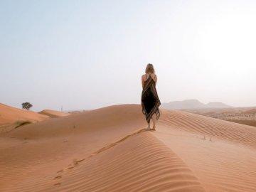 Samotność - Kobieta spaceru na pustyni w ciągu dnia. UK