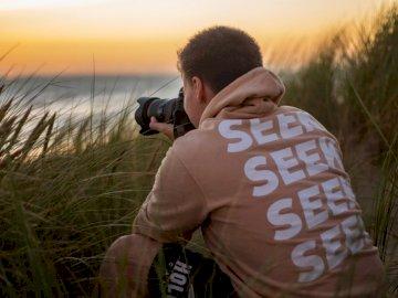 Ich und mein Freund James gingen - Mann im orange Suchhemd sitzend, das DSLR-Kamera hält.