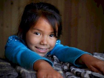 Danielita de Icalma - Girl wearing blue sweater with hands on gray bedspread. Viña del Mar, Chile