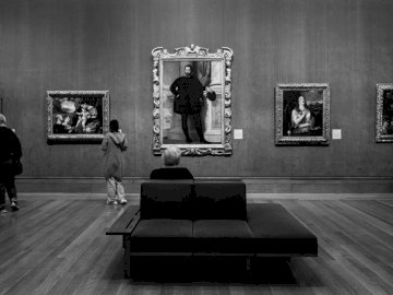 Black and White Museum - Grayscale photo of man sitting on black leather couch.