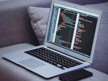 Codifica, tecnologia - MacBook Air su poltrona grigia. Croazia