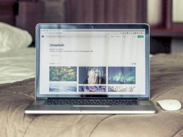 Una foto Unsplash in un - MacBook Pro sul letto grigio. Olanda