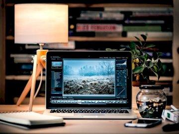 Computer portatile per il fotoritocco - MacBook Pro sul tavolo di legno marrone all'interno della stanza. Polonia