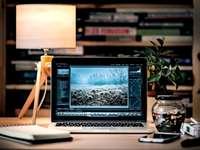Fotószerkesztő laptop - MacBook Pro egy barna fából készült asztal a szobában. Lengyelország