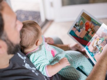 Story Time with Daddy - Person carrying baby while reading book. Los Angeles, CA