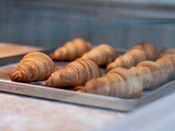 Flockige Croissants - Sieben Croissants auf grauem Metalltablett. Lemberg, Ukraine