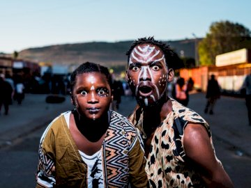 People of Mamelodi, Pretoria - Two people with face paints taking photo in street. Johannesburg, South Africa