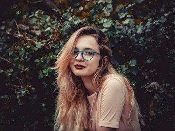 Modèle - @ariveola - Femme debout à côté d'un buisson vert.