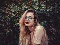 Modell - @ariveola - Kvinna som står bredvid den gröna busken.