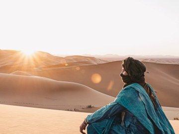 Pustynia, natura - Kobiety w niebieskim kapturem, siedząc na piasku podczas zachodu słońca. Marrakesz