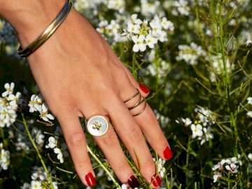 The Hand that Rocks the - Woman touching white petaled flower.