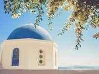 Ελληνικός θόλος κάτω από το δέντρο - Μια φωτογραφία του άσπρου και μπλε καθεδρικού ναού. Μπ�