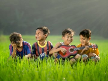Jakarta shoot - Four boys laughing and sitting on grass during daytime.