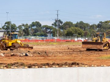 Dozers at work on construction - Yellow and black heavy equipment on brown field during daytime. Melbourne, Australia